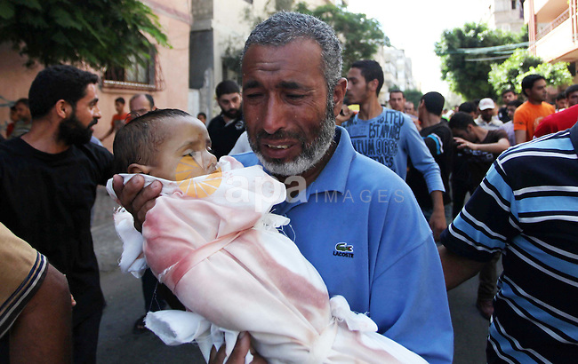 A Palestinian man carries the body of one-year-old baby Noha Mesleh, who died after a UN school in Beit Hanun was hit by an Israeli tank shell, during her funeral in Beit Lahia, northern Gaza Strip, on July 25, 2014. Fifteen people were killed when Israeli fire hit a UN-run school in Gaza, raising the Palestinian toll on the 17th day of the conflict to 777, medics said. Photo by Ashraf Amra