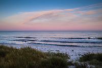 Havsvågor mot sandstrand i skymning över havet på Österlen Skåne