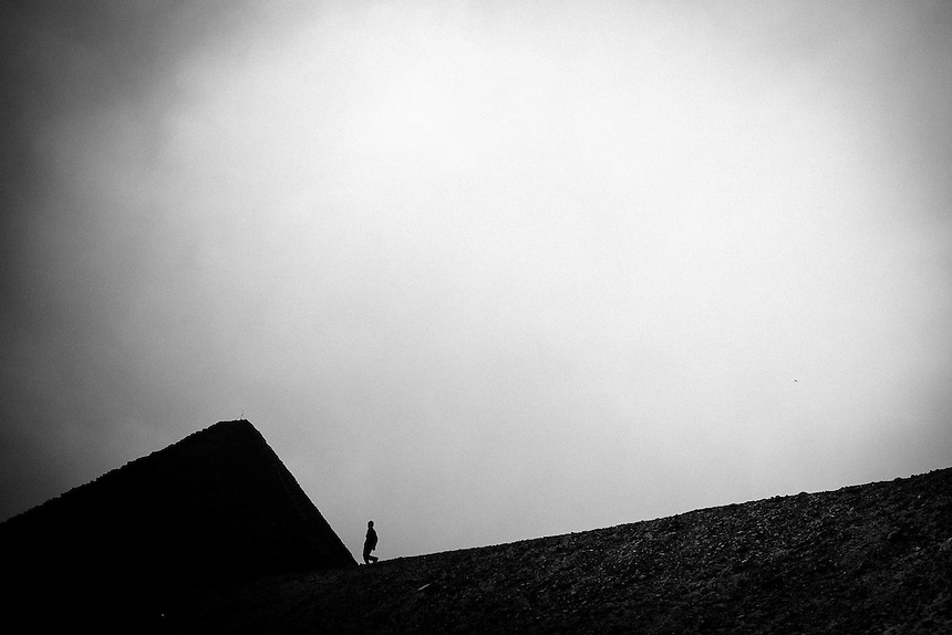 A man walks down a slope toward the Great Pyramid of Cheops on the Giza plateau, Cairo, Egypt, September 2011. Photo: Ed Giles.