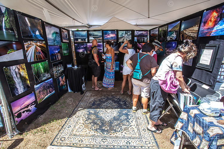 People browse artwork at Mike Krzywonski Photography's booth at the 16th Annual Haleiwa Arts Festival at Haleiwa Beach Park, North Shore, O'ahu.