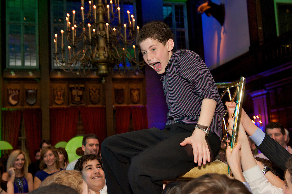 The Bar Mitzvah boy being lifted in a chair during the hora dance.