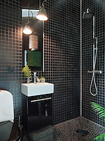 The mirror in the mosaic tiled bathroom is lit by an industrial lamp, altered to fit the room
