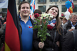 A couple with a German flag waiting for the speeches to begin before a demonstration by the Alternative für Deutschland (AfD) political party in Berlin. Around 5000 supporters of the AfD took part in the march and rally through central Berlin calling on German Chancellor Angela Merkel to halt the influx of refugees into the country. Around one million refugees from the Middle East and north Africa arrived in Germany during 2015, 50,000 of whom came to Berlin.