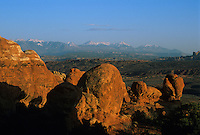Rocks lit by warm evening glow & snowy mountains-Arches National Park, Utah