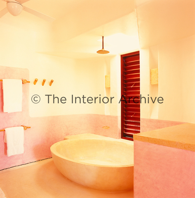 The large sculpted bath is the main feature of this bathroom which is partly painted in a subtle shade of pink