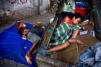 Kartini Emergency School first grade student, 10 year old Sarmiah takes an afternoon nap inside the pushcart used to keep discarded materials collected by her scavenger father. Sleeping on the pavement are her father and younger brother Joko, who's also a student at Kartini. After their mother died from Tuberculosis (TB), Sarmiah's father, who spent what little money the family had on medication for his wife, had to give up their rented home and now lives on the streets. Since the early 1990s, twin sisters Sri Rosyati (known as Rossy) and Sri Irianingsih (known as Rian) have used their family inheritance to set up and run 64 schools in different parts of Indonesia, providing primary education combined with practical skills to some of the country's most deprived children.