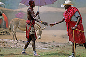 Lolgorian, Kenya. Siria Maasai greeting a fellow tribesman with an umbrella at the manyatta set up for the eunoto ceremony.
