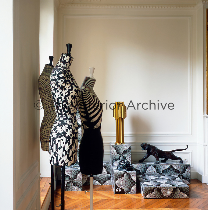 Graphic patterns, added to a simple palette of white, black and gold create an elegant combination. Three Stockman mannequins designed by artist Emmanuel Bossuet stand to one side