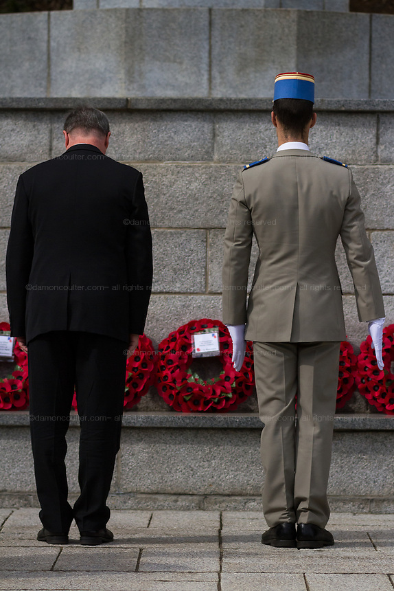 A French soldier and diplomat lay a wreath of poppies at the Cross of Sacrifice during the  Remembrance Sunday ceremony at the Hodogaya, Commonwealth War Graves Cemetery in Hodogaya, Yokohama, Kanagawa, Japan. Sunday November 12th 2017. The Hodagaya Cemetery holds the remains of more than 1500 servicemen and women, from the Commonwealth but also from Holland and the United States, who died as prisoners of war or during the Allied occupation of Japan. Each year officials from the British and Commonwealth embassies, the British Legion and the British Chamber of Commerce honour the dead at a ceremony in this beautiful cemetery.