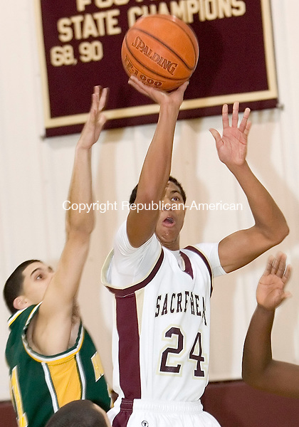 WATERBURY, CT- 02 JAN 2008- 010208JT11-<br /> Sacred Heart's Bryant Corcoran shoots as Holy Cross' Rob Mannetti reaches for the ball behind him during Wednesday's game at Sacred Heart. Cross remains undefeated, beating Sacred Heart 61-46. <br /> Josalee Thrift / Republican-American