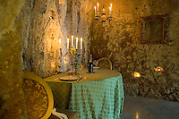 A romantic table for two stands in this grotto dining room and is lit by a silver candelabra