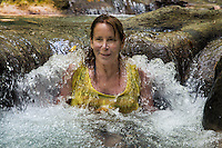 Woman enjoys a refreshing water massage at Mayfield Falls, Glenbrook, Jamaica