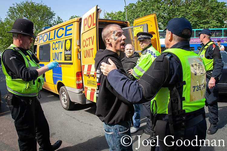 © Joel Goodman - 07973 332324 . 02/06/2012 . Brighton , UK . Police detain a man wearing an EDL hoodie . Groups of nationalists , including supporters of March for England and the EDL , congregate in Brighton as anti-fascist and left-wing campaigners supporting UK Uncut also congregate . An intensive policing operation is deployed to separate opposing left and right wing groups . Photo credit: Joel Goodman