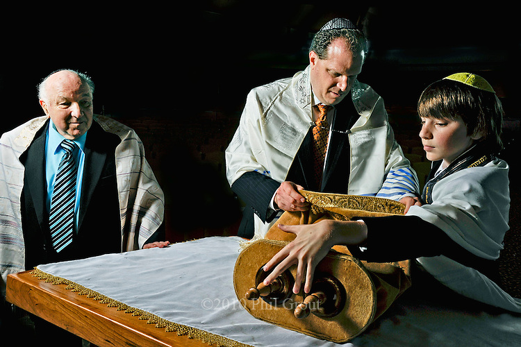 Mitchell Traub and his father, Freddie, store the Torah as grandfather, Jerry Traub, observes the ancient Jewish ritual.