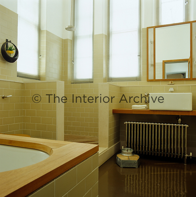 The large walk-in shower is entirely clad in beige ceramic tiles to match the rest of the bathroom where light floods in from two sides via a series of long windows screened with Venetian blinds