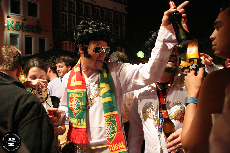 "USA National Soccer Team fan, (left to right) Pat Ryan of Kansas City, MO,  dressed up in flight suits as the American Icon Elvis, enjoys some late night celebrating at a beer garden in Cologne, Germany on Monday, June 12th, 2006  with fans from several other countries.  The fans were part of a tour group arraigned by Pat Ryan from Kansas City, MO called ""2006 World Cup Trip."" They were among the thousands of American fans who have descended on Germany to support the USA National team during the 2006 FIFA World Cup."
