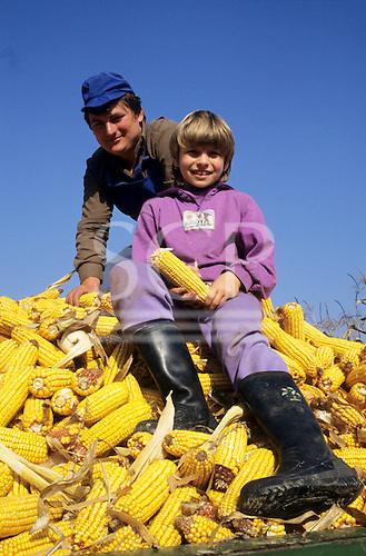 Slovenia. Smiling farmer and daughter on a trailer load of sweetcorn (maize).