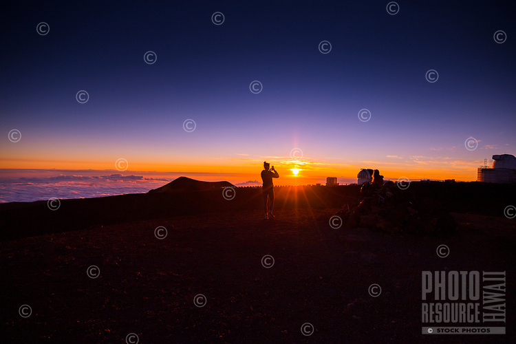 A visitor takes a photo of a glowing sunset from Mauna Kea, Big Island.