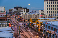 A near full moon sets over downtown Anchorage, Alaska 4th Avenue. Winter  Cityscape