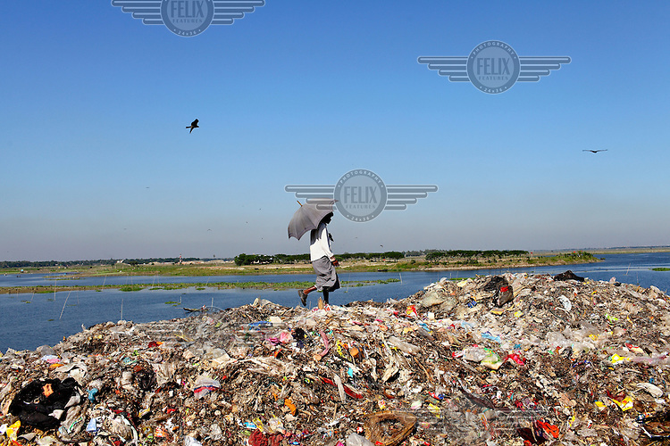 A man walking beneath an umbrella looking for recyclable material at the biggest rubbish dump in Dhaka. The city alone generates about 3500 to 4000 metric tons of solid waste each day.