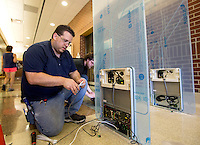 NWA Democrat-Gazette/JASON IVESTER <br /> Jason Oles (cq) (left) and Ian Schenholm (cq), both with Atlanta-based Bibliotheca, install a Smartgate 400 on Wednesday, Sept. 16, 2015, near the entrance inside the Bentonville Public Library. The new security gates, which use radio frequency indentification (RFID) for library materials, are part of a phased technology upgrade for the library.