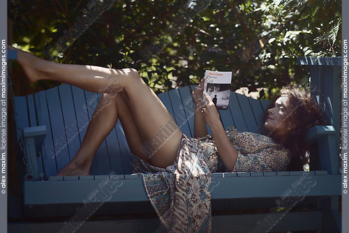 Sensual portrait of a beautiful young woman reading a book lying on a garden bench in a shade