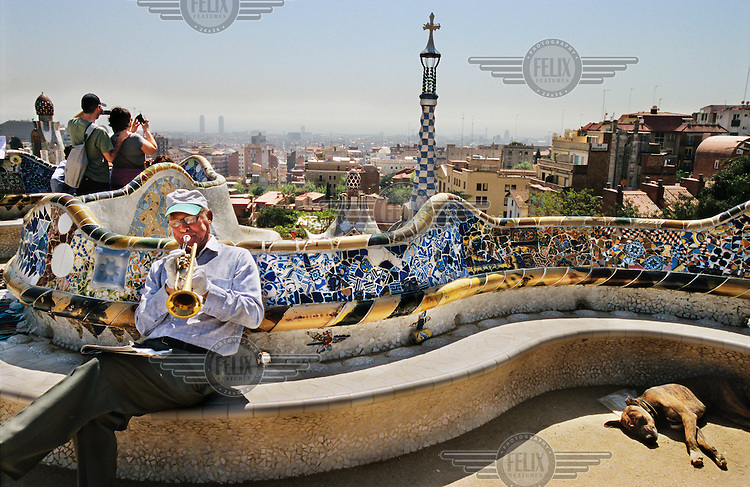 A dog sleeps beside a man playing a trumpet in the Parc Guell. The park was designed by Antoni Gaudi and built in the years 1900 to 1914. Its focal point is the main terrace, surrounded by a long mosaic bench in the form of a sea serpent.