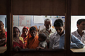 25 year old Dayawati (centre) and her 17 month son, Naresh Mukhiya wait with other caregivers and family members who wait to get medicines and other medical benefits at the local health centre in Hanuman Nagar in Saptari, Nepal. <br /> Naresh Mukhiya was first admitted on July 17, 2013 when he was 9 months old. MUAC - 109 mm, Weight - 5.5kg, and Height - 65 cm. He was discharged on Oct 1st, 2013. MUAC at the time of discharge - 123, Weight - 6.5 Kg, Height - 66cm. Total RUTF consumes - 148 sachets.Gain of weight - 2gm.day.