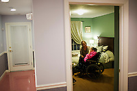 Caregiver Laurie Okonoboh cares for the hands of resident Kathy Bunker, 57, in Kathy's bedroom at an assisted living home run by Northeast Residential Services in Bedford, Massachusetts, USA.  The residents previously lived at the Fernald Developmental Center in Waltham, Massachusetts, USA.