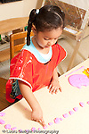 Education preschool 3-4 year olds art activity girl playing with play dough pointing to count each piece vertical
