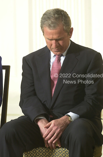 United States President George W. Bush bows his head in prayer at a reception celebrating the 50th Anniversary of the National Day of Prayer in the East Room at the White House in Washington, D.C. on May 3, 2001..Credit: Ron Sachs / CNP