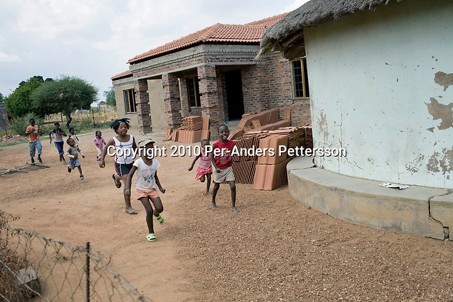 GA-MASEHLONG, SOUTH AFRICA - MARCH 28: Children play outside the newly constructed house for Caster Semenya on March 28, 2010, in Ga-Masehlong, South Africa. Caster Semenya, age 19, a runner who won the 800 meters world cup title in Berlin, Germany in 2009. She was later gender tested as she blew away the competition. She has not competed in any race since then but she is still a role model for relatives and children in this rural poor village. She was raised in the traditional hut on the right and the newly constructed house is a gift from the local government. (Photo by Per-Anders Pettersson/Getty Images)