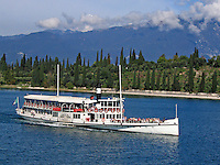 Lake Garda, Italy, ferry, ferry boat, paddle steamer, lake, blue sky, trees, forest, shoreline, coastline, mountains, blue sky, white clouds, 200609180047.<br />