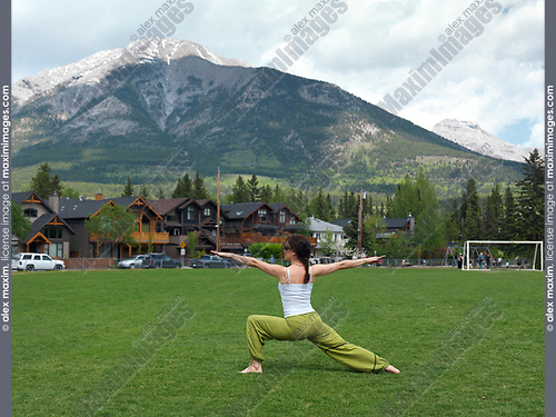 Young woman practicing yoga warrior posture outdoors in Centennial Park in Canmore, town in Alberta's Rockies with Rocky mountains in the background. Canmore, Alberta, Canada. 2017