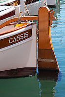 In the harbour in Cassis village.  A traditional style boat with wooden rudder marked with the name Cassis. Painted white. Cassis Cote d'Azur Var France Bouches du Rhone