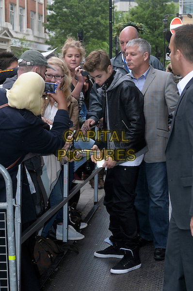 Justin Bieber at BBC Radio 1, London, England..June 6th, 2012.full length black jacket jeans denim grey gray hood fans signing autographs leather profile minder security bodyguards .CAP/IA.©Ian Allis/Capital Pictures.