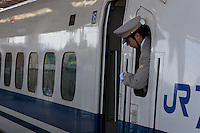 A guard checks his watch as he looks out of the window of a JR 700  class Shinkansen bullet train at Shin-Yokohama station, Yokohama, Japan. August 14th 2008