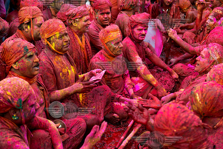 Devotees, covered in the bright dyes that are joyfully spread, thrown and sprayed about during Lathmar Holi, gather at the Krishna Temple of Shriji, during the festival which is an annual riot of colour and frenzied celebration of spring, fertility and the triumph of good over evil.