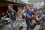 "Larren Jo ""LJ"" Bacilio, a teacher in the Alternative Learning System of the Kapatiran-Kaunlaran Foundation (KKFI), walks with some of his students in the Tondo neighborhood of Manila, Philippines. <br /> <br /> KKFI is supported by United Methodist Women."