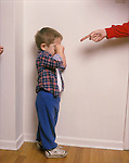 Tearful 2 year old boy being scolded and disciplined by parent