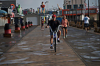 A man rides bikecicle along a boardwalkin in Seaside Heights September 13, 2013 by Kena Betancur / VIEWpress