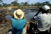 Lukulu, Zambia. Tourists looking for wildlife with binoculars beside a stream.