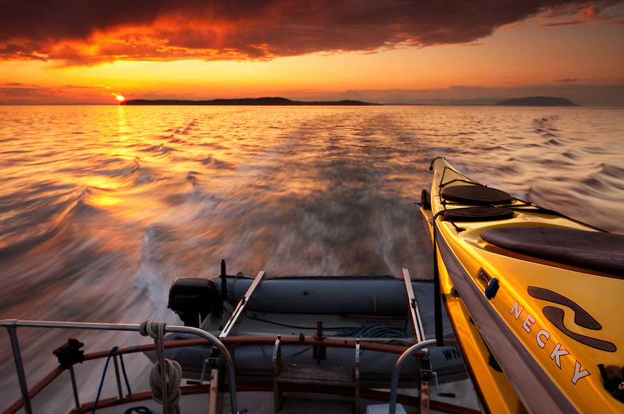 Necky Kayaks mounted on the back of a large boat are lit by the setting sun outside Vancouver Island.