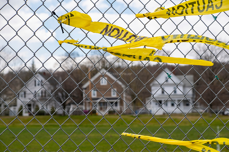Caution tape is seen on a fence with residential houses in the background during the ongoing Coronavirus (COVID-19) global pandemic in Belmont, Massachusetts, on Thu., April 16, 2020. The fence surrounds Belmont's Town Field, one of the many parks and playgrounds closed to the public for the duration of the pandemic as a way to enforce social distancing protocols.