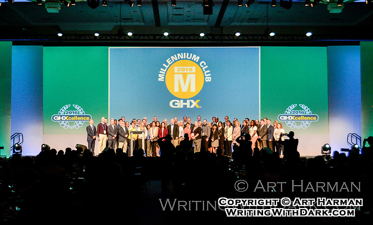 Awards banquet presentation. A wide shot like this plus closeups of recipients make for the right set of photos to promote your event. Work with the MC to make sure everyone lines up and poses neatly.