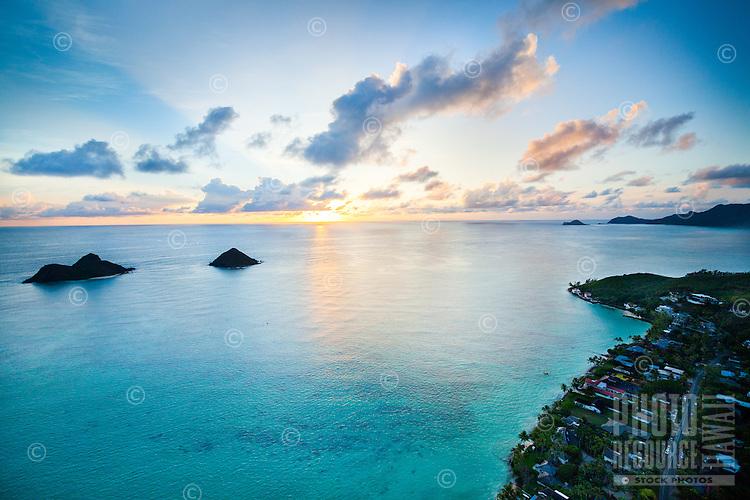 An aerial view of sunrise off of Windward O'ahu near the Mokuluas (or Na Mokulua) and Lanikai neighborhood.