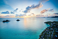 An aerial view of sunrise off of Windward O'ahu near the Mokuluas (or Na Mokulua) and Lanikai neighborhood.