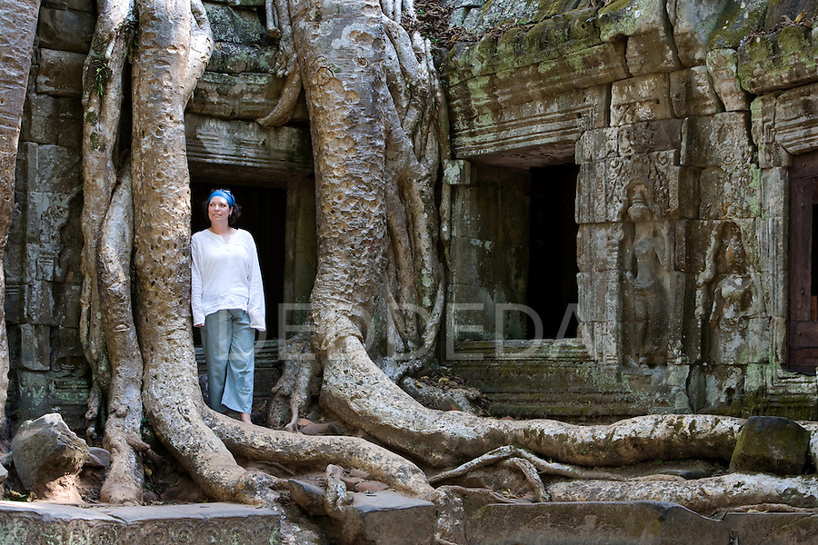 A female tourist stands next to a temple in the ancient city of Angkor Thom, Cambodia.