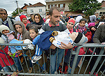 A father holds his child as he and other people await entry to a refugee processing center in the Serbian village of Presevo, not far from the Macedonian border. Hundreds of thousands of refugees and migrants have flowed through Serbia in 2015, on their way from Syria, Iraq and other countries to western Europe.