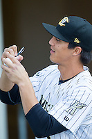 Tyler Saladino (8) of the Charlotte Knights autographs a baseball prior to the game against the Louisville Bats at BB&T Ballpark on June 26, 2014 in Charlotte, North Carolina.  The Bats defeated the Knights 6-4.  (Brian Westerholt/Four Seam Images)